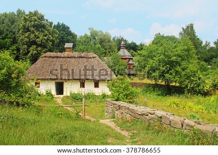Old traditional house and church in Ukraine - stock photo