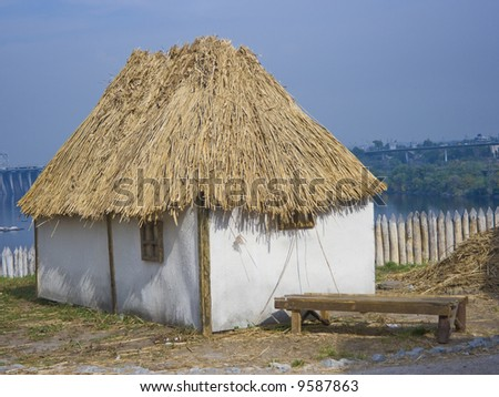old traditional ukrainian house with thatched roof - stock photo