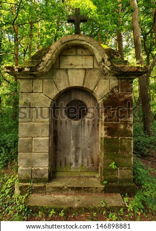 Old traditional village chapel in the park at old graveyard in shadows of old alder trees and lindens. Door with rusty forged gate is closed.