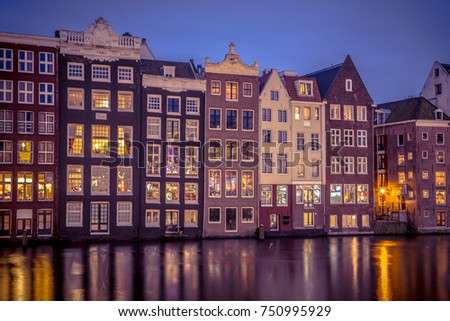 Old traditional vintage colored canal houses at night in the UNESCO World Heritage site of Amsterdam