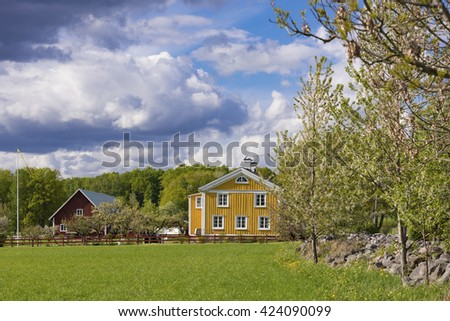 Old traditional wooden farmhouse in Sweden. Yellow painted traditional farmhouse in the Swedish countryside.  - stock photo