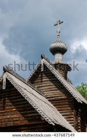 Old traditional wooden Russian Orthodox church roof with a cross on the dome - stock photo