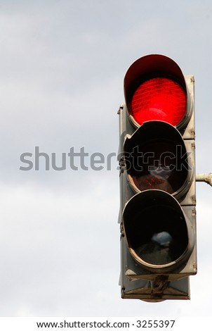 Old traffic light on  background of  grey sky, red signal - stock photo
