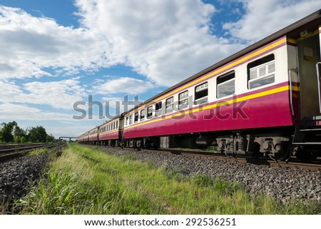 Old train engine and rail track in rural of Thailand with white cloud and blue sky background - stock photo