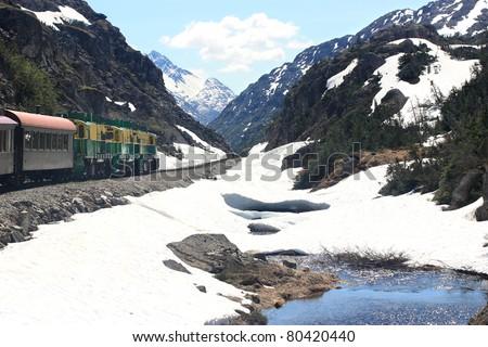 Old train traveling through snowy mountain - stock photo