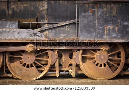 Old train wheels and parts rusting away - stock photo