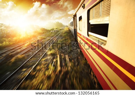 Old train with opened windows and motion blurred railways at sunrise - stock photo