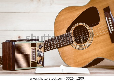 Old transistor radio and Acoustic guitar on wooden background. Retro Style. - stock photo