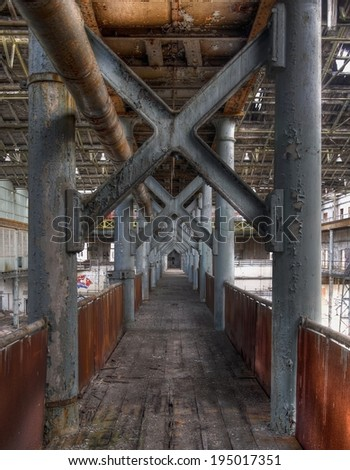 Old transition in an abandoned hall with steel posts - stock photo