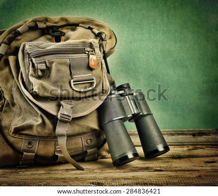 Old travel backpack and binoculars on the floor. Toned - stock photo