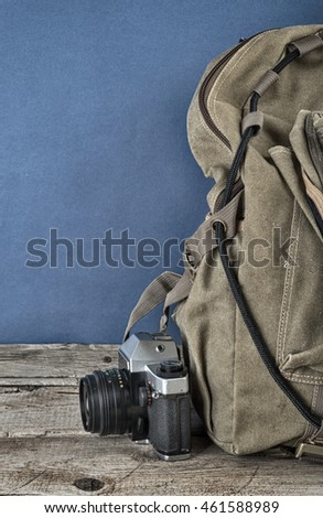 Old travel backpack  and camera on the wooden floor. Toned