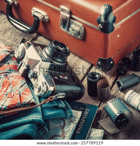 Old travel suitcase, sneakers, clothing, map, filmstrip and retro film camera on wooden background. Vintage stylized. - stock photo