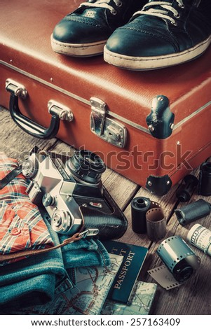 Old travel suitcase, sneakers, clothing, map, filmstrip and retro film camera. Vintage stylized. - stock photo