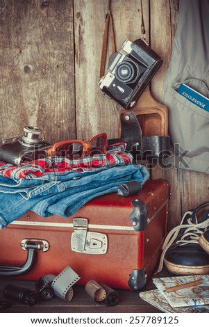 Old travel suitcase, sneakers, clothing, sunglasses, maps, filmstrip and retro film camera . Vintage stylized. - stock photo