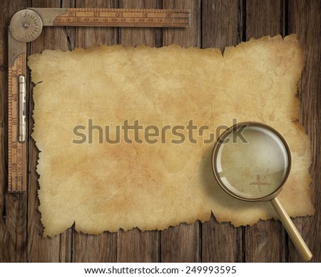 old treasure map on wooden desk with loupe and ruler