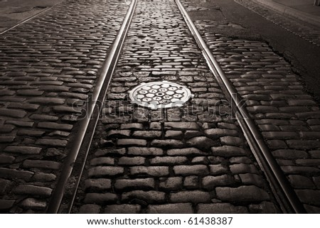 Old trolley tracks and cobblestones survive under the flaking asphalt pavement of this Brooklyn Heights street, Brooklyn, New York. A night time exposure. - stock photo