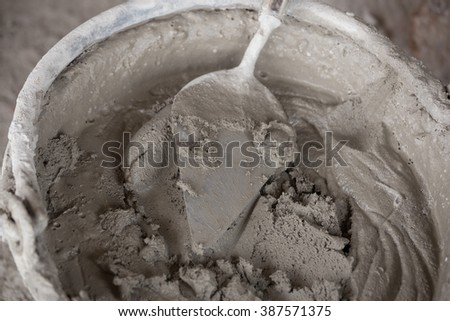 old trowel and bucket with mortar at consturction site - stock photo
