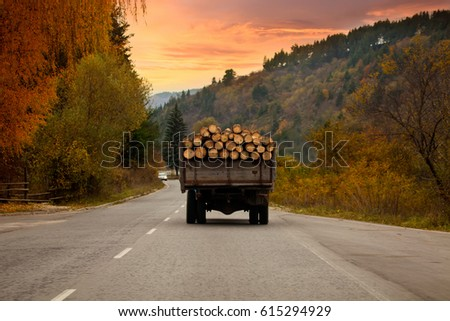 old truck full with wooden logs travel trough bulgarian roads, autumn sunset time