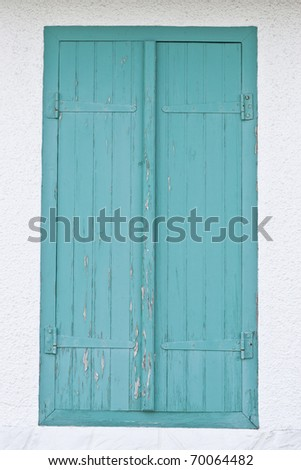 old turquoise window made out of wood on white wall - stock photo