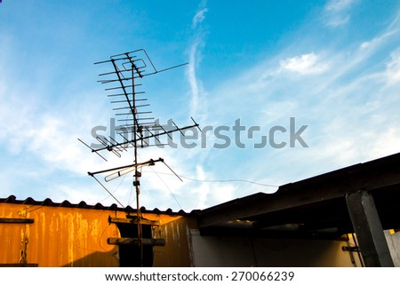 Old TV antenna on the roof and blue sky white cloud background - stock photo