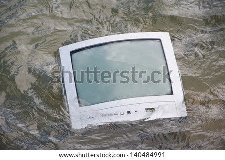 old TV is swimming in water - stock photo