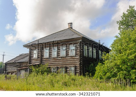 Old two-storey wooden house with slate roof in the northern Russian village, summer time - stock photo