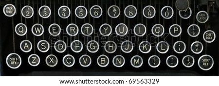 old typewriter keyboard with silver and black round keys with a black background - stock photo