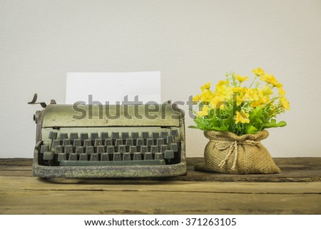 Old typewriter with blank paper,Old retro typewriter on table on white background,Retro typewriter placed on wooden planks,Vintage typewriter and a blank sheet of paper,vintage tone,selective focus. - stock photo