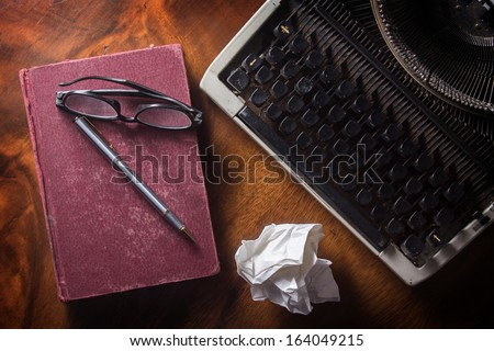 Old typewriter with book,pen and eyeglasses on top view. - stock photo