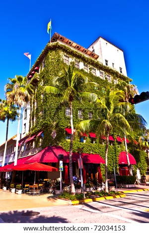 old typical building in art deco style in South Miami with climbing plants and a cafe - stock photo