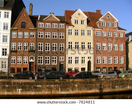 Old typical facades of charming buildings in the old center of Copenhagen on a sunny day next to the canal