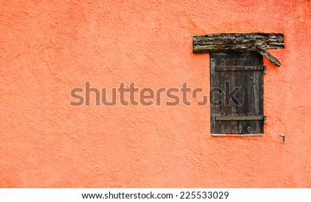 Old typical Mediterranean house with ocher stucco wall and closed wooden shutters. - stock photo