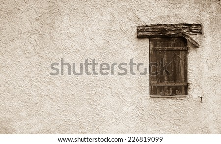 Old typical Mediterranean house with stucco wall and closed wooden shutters. Aged photo. Sepia. - stock photo