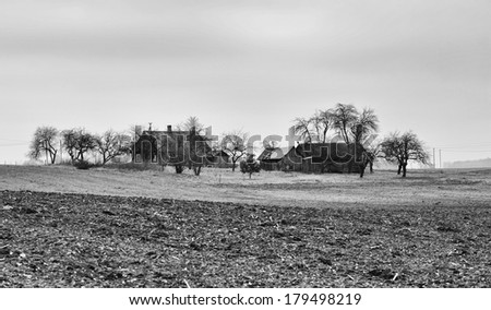 Old typical village view in Lithuania, old wood houses in empty autumn fields, old village photo in black in white, B&W photo, Lithuania, typical village in Lithuania, Alytus, empty field in autumn - stock photo