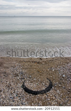 old tyre on the sea shore - stock photo