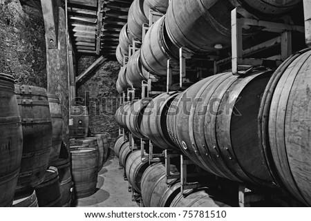 old underground wine storage cave with racks of wooden barrels - stock photo