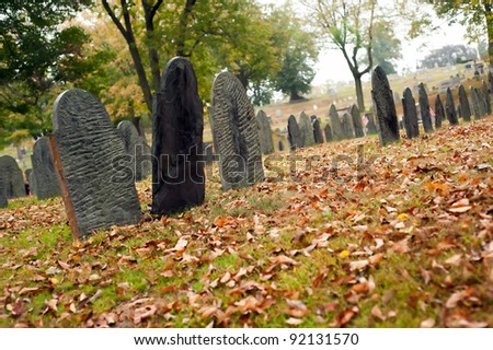 Old unmarked gravestones in an old cemetery during autumn. - stock photo