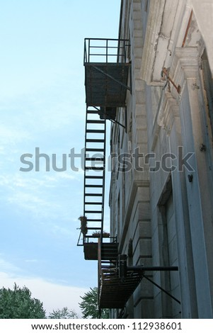 Old urban building in Montreal with metal fire escape - stock photo