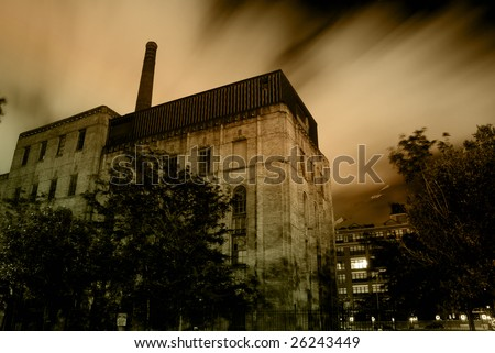 Old urban industrial building with dramatic night sky and clouds - stock photo