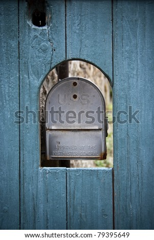Old Us mailbox in an ancient blue wooden door