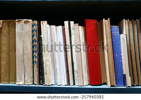 Old used books on bookshelf in library - stock photo