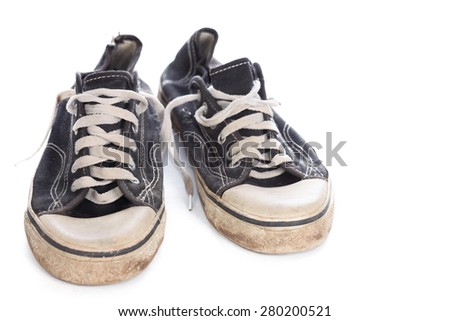 Old used dirty gumshoes with lacing, isolated, on white background