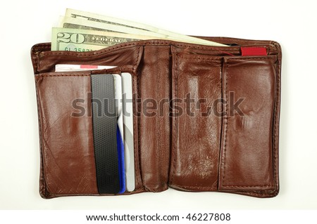 Old used genuine leather wallet containing various cards and money - stock photo