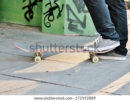 Old used skateboard isolated on the ground - stock photo