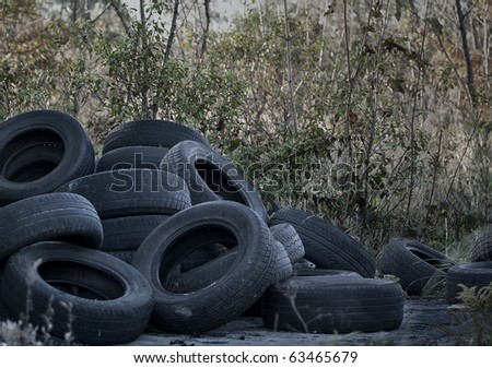 Old used tires dumped in the meadow - stock photo