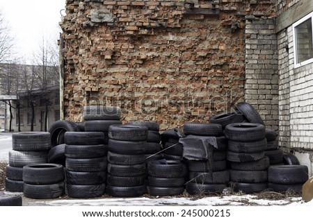 Old used tires stocked for recycling at red brick wall - stock photo
