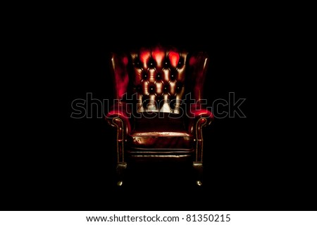 Old used vintage red leather chair on black background - stock photo
