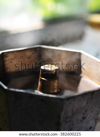 old used vintage retro dirty white aluminum Italian espresso coffee pot during cooking boiling coffee on the stove with hot coffee and steam flowing from the top opening tube in the metal machine - stock photo
