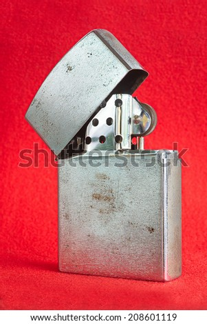Old Used vintage Silver metal lighter red background smoker zippo light open burn one used tobacco macro equipment wheel object gas gasoline shiny metallic - stock photo