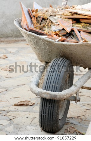 old used wheelbarrow details with construction waste, broken tiles pieces - stock photo